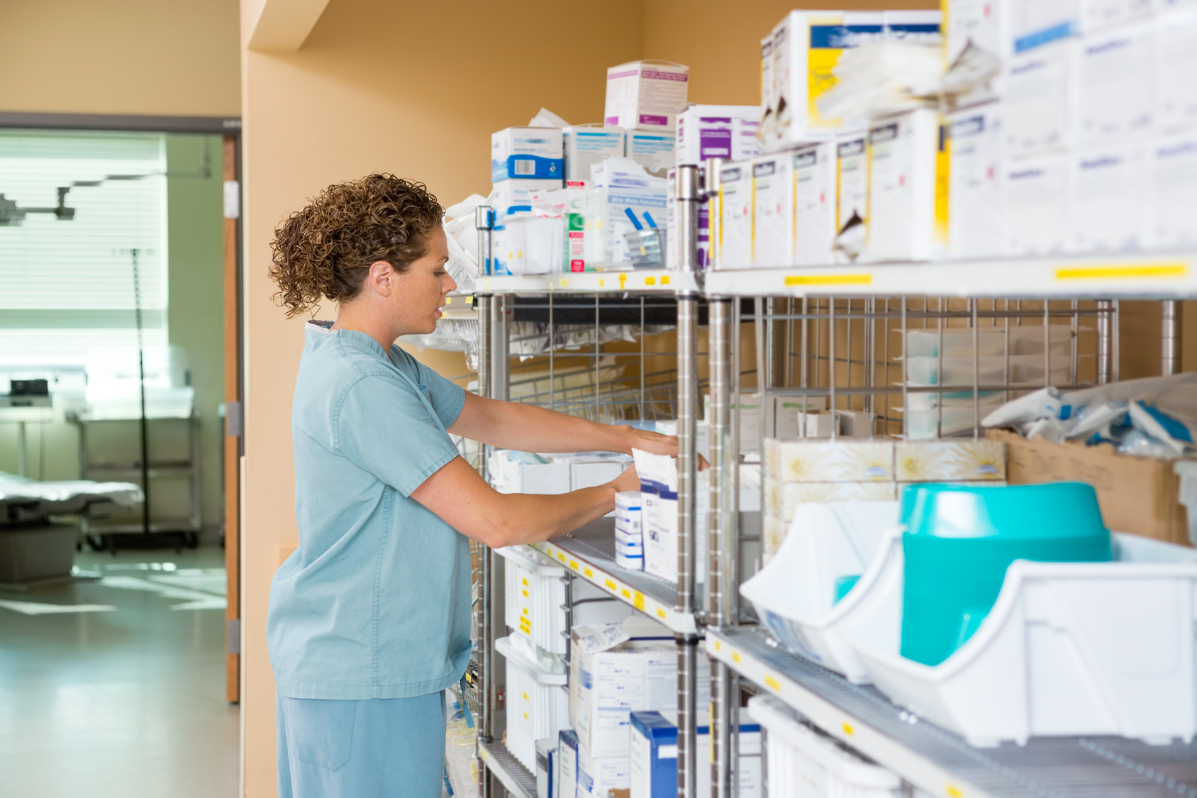 5f745c610a8 Side view of mid adult female nurse working in storage room of cancer  hospital
